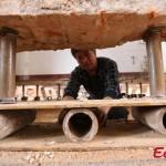 Trong ảnh là các chuyên gia đang tạo hệ thống con lăn bằng cách đặt ống sắt dưới ván gỗ